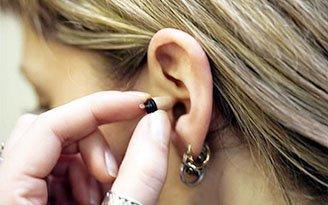 inserimento di un micro auricolare spia nel canale uditivo
